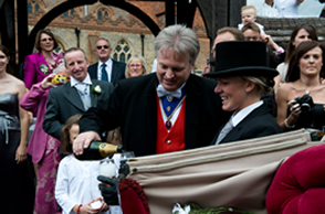 Essex toastmaster Richard Palmer pouring champagne for the bride and bridegroom outside Great Baddow Church, Essex