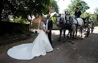 Bride and bridegroom posing for the photographer in front of their horse drawn carriage