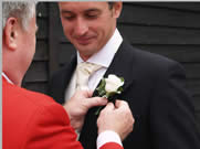 Wedding Toastmaster assists guest with button hole at Vaulty Manor, Essex