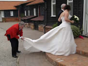Essex Wedding Toastmaster assists bride with her wedding dress at Vaulty Manor, Essex